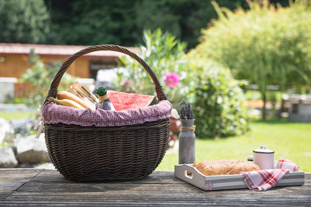 Picnic basket and bread on wooden table in the garden