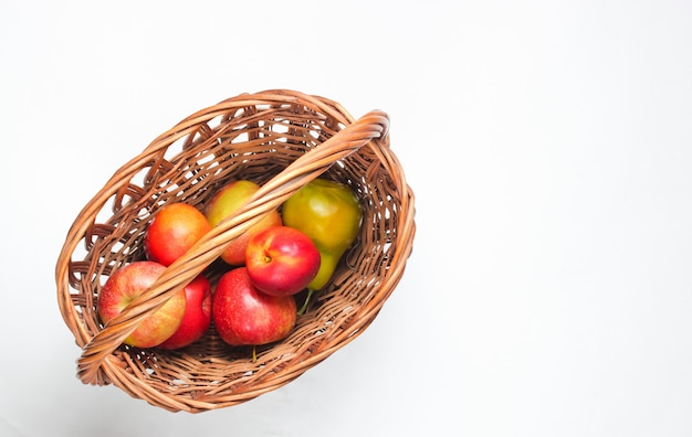 Picnic basket filled with fruits on a white background.