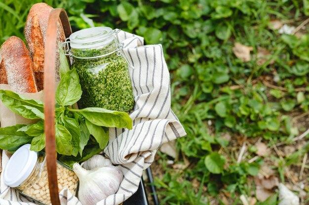 焼きたてのガーリックブレッドまたはブルスケッタを準備するためのピクニックバスケット、伝統的なイタリアンソースのバゲット前菜-バジル、松の実、屋外のパンを材料にしたガラスの瓶に入った自家製ペスト。