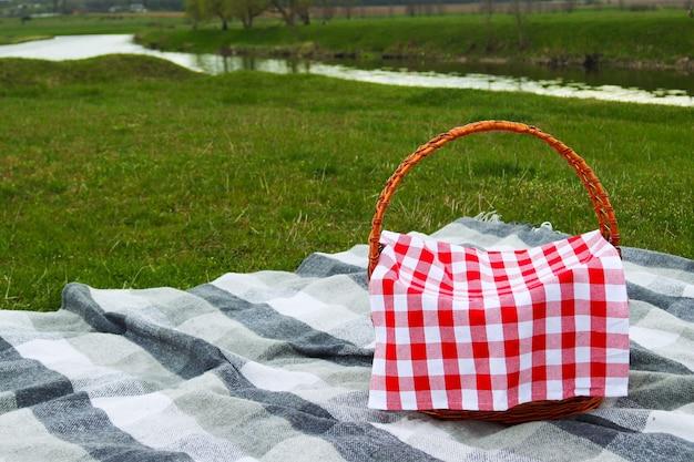 川のコピースペース近くの牧草地にある灰色の市松模様の毛布にピクニックバスケット