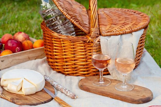 Корзина для пикника с различными закусками на зеленой траве в саду