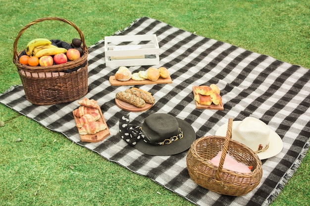 Picnic basket with fresh fruits; baked breads and hat on blanket over the green grass