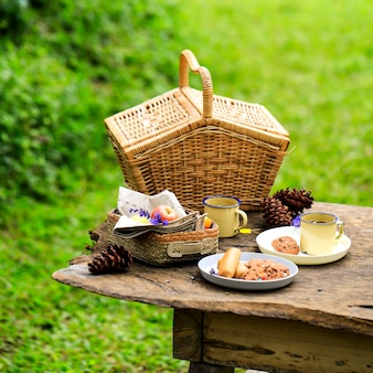 Picnic basket with fruit and bakery on old rustic wooden table with green scenery