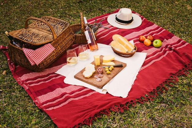 Picnic basket with goodies on red blanket