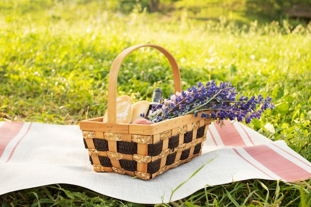 Picnic basket with lupinus, baguette, wine on a tablecloth on a background of green grass