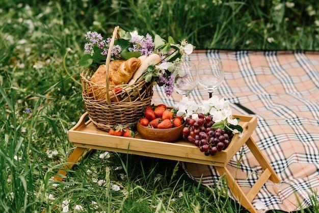 イチゴ、ブドウ、庭の緑の芝生の上のパンのピクニックバスケット