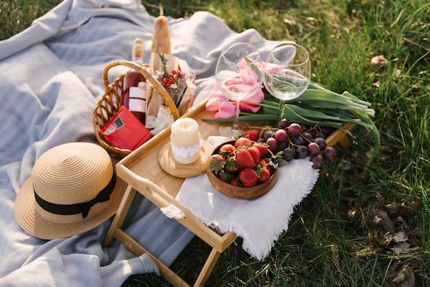 Корзина для пикника с клубникой, виноградом и булочками на зеленой траве в саду