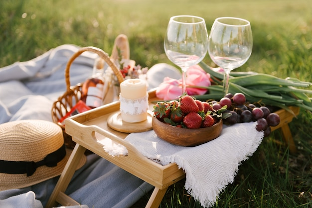 Picnic basket with strawberries, grapes and buns on the green grass in the garden