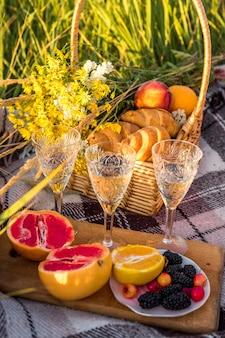 緑の日当たりの良い芝生の上に2つのクロワッサン、グレープフルーツ、オレンジ、ベリー、シャンパンとガラスのピクニックバスケット