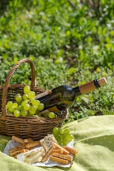 ワイン、チーズ、ブドウのピクニックバスケット Premium写真