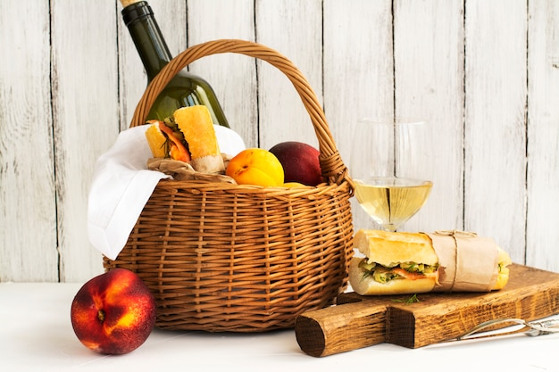 Picnic basket with wine, salmon sandwiches and fruits over white
