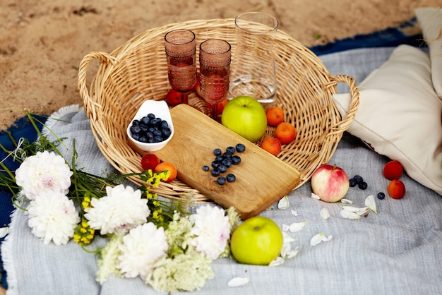Picnic on the beach blankets.  basket with berries fruits and wine glasses on a plaid