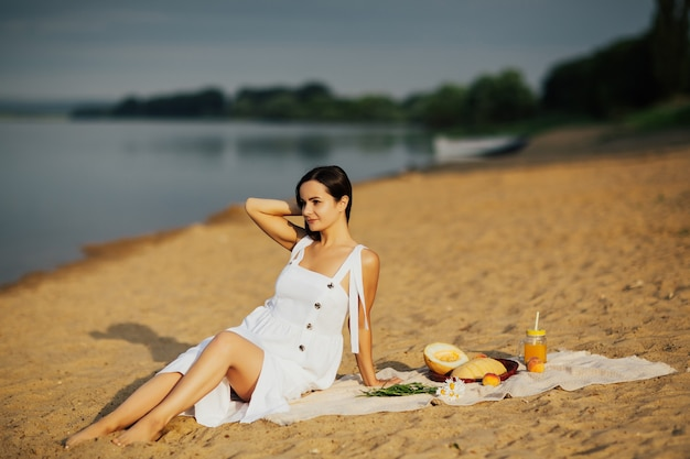 Picnic on the beach. romantic woman in white dress sitting on cover on the beach in summer sunny day.