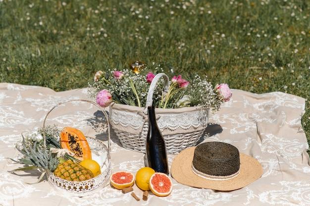 Одеяло для пикника на лужайке с корзиной, полной цветов, тропических фруктов, соломенной шляпой и бутылкой вина.