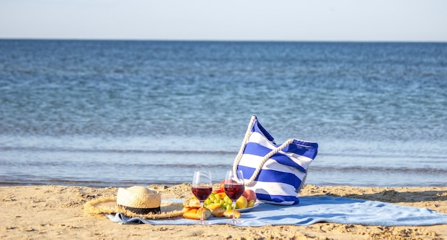 Одеяло для пикника, вино, фрукты, красивый морской пляж природа выборочный фокус