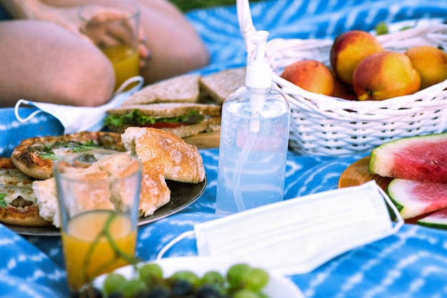 Picnic blanket with goodies and disinfectant for hands
