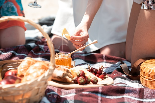 Picnic bread, croissant basket with fruit on cloth with bright sunlight. croissant, honey, strawberry. healthy choice for spending time on nature in summer day. food, nutrition, healthy eating.