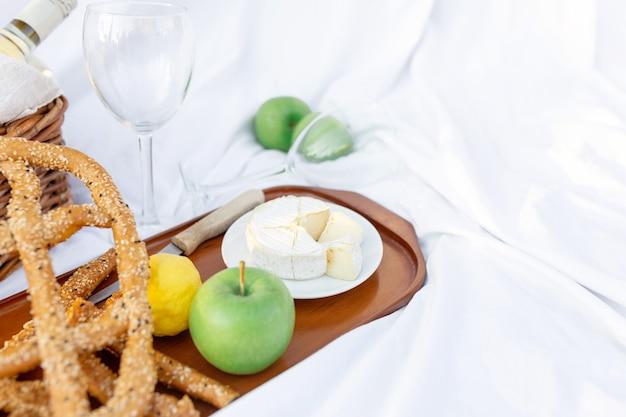 Завтрак-пикник на рассвете, на траве белый лист с подносом с сыром и виноградом, сухой хлеб, яблоко, лимон. романтическое настроение, эстетическая концепция неспешного образа жизни, вид сверху