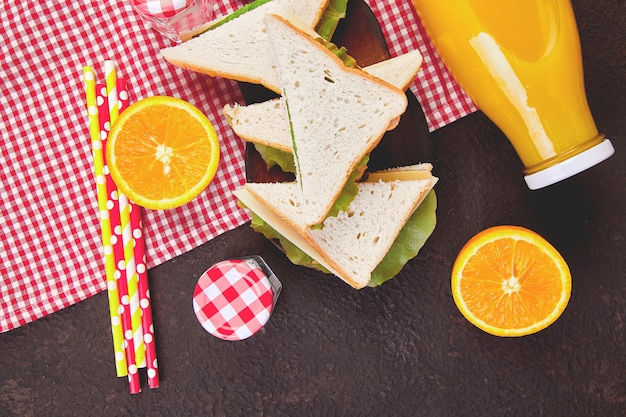 Picnic on brown table. red checked tablecloth, basket, healthy food sandwich and fruit, orange juice.  summer time rest. flat lay