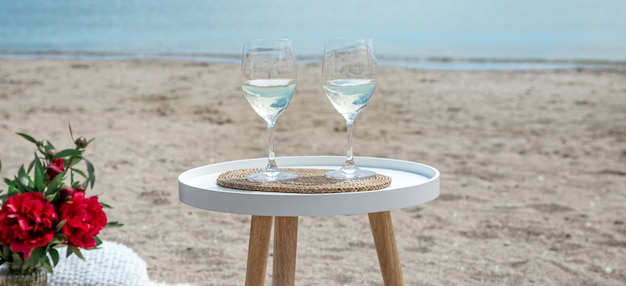 꽃과 샴페인 한 잔과 함께 바다에서 피크닉. 휴일의 개념.