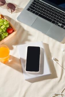ピクニックのコンセプトと明るい背景にラップトップ、電話、ジュース、フルーツ、イヤホンで夏休み。