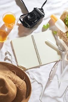 ピクニックのコンセプト。帽子、日焼け止めクリーム、フルーツバッグ、ジュース、ノートブック、カメラ、白い背景の上の日焼け止めクリーム。