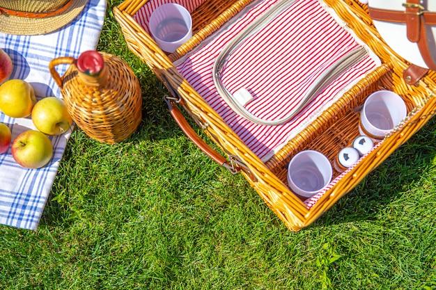 공원에서 녹색 햇볕이 잘 드는 잔디밭에 바구니와 피크닉 개념