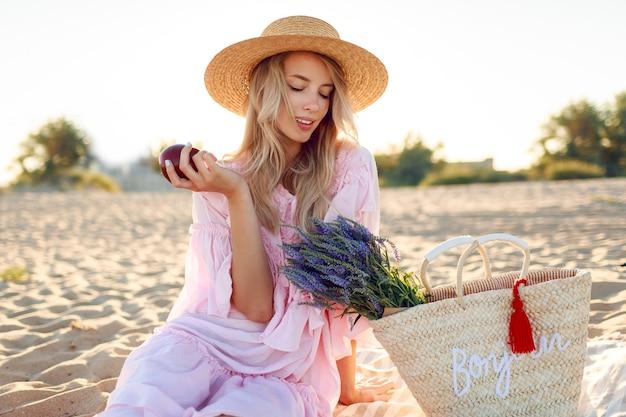 Picnic in campagna vicino all'oceano. graziosa giovane donna con i capelli biondi ondulati in elegante abito rosa godendo le vacanze e mangiando frutta.