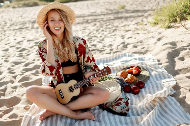 Picnic in countryside. romantic blonde woman in straw hat sitting on cover on the beach in sunset soft colors and playing ukulele guitar. fresh fruits, croissants and peach on the plate.