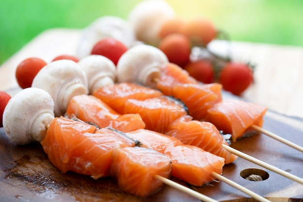 Picnic food, skewers raw salmon with mushroom and tomatoes on chopping board