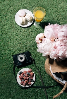 Picnic on the grass berries and peonies