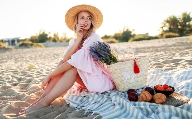 바다 근처 시골에서 피크닉. 휴일을 즐기고 과일을 먹는 우아한 핑크 드레스에 금발 물결 모양의 머리카락을 가진 우아한 젊은 여자.