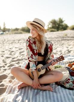 田舎でのピクニック。夕焼けの柔らかな色でビーチのカバーに座ってウクレレギターを弾く麦わら帽子のロマンチックなブロンドの女性。プレートに新鮮なフルーツ、クロワッサン、ピーチ。