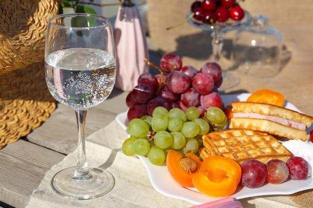 自然の中でのピクニック。黄麻布の上に果物とワッフルとコップ一杯の水が立つプレート