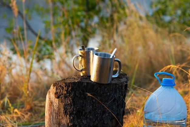 자연에서 피크닉입니다. 숟가락이 달린 두 개의 금속 열 컵이 나무 그루터기에 서 있습니다.
