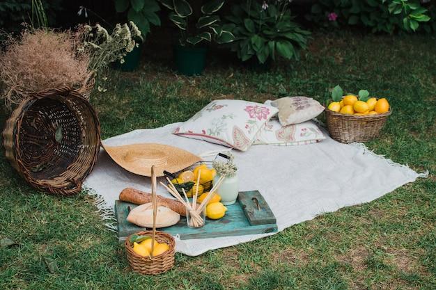 Пикник на природе белое покрывало с корзинами и лимонами концепция летнего отдыха