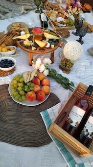 かわいい女性の装飾が施された自然の中でのピクニック。フルーツ、ワイン、チーズ、おやつ、キャンドル