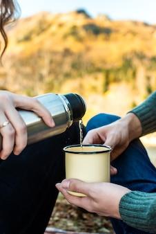 秋の森でのピクニック。女性の手が魔法瓶からレトロなマグカップにお茶を注ぎます。ロマンチックな散歩の秋