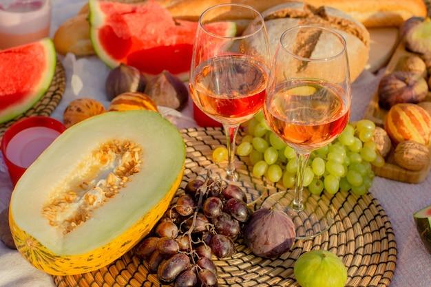 牧草地でのワインとフルーツのピクニック