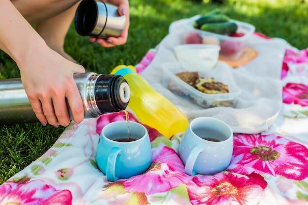 公園でのピクニック。女性の手は魔法瓶から青いマグカップにお茶を注ぎます。おいしいディナー。夏休み。屋外レクリエーション、旅行、料理のコンセプト