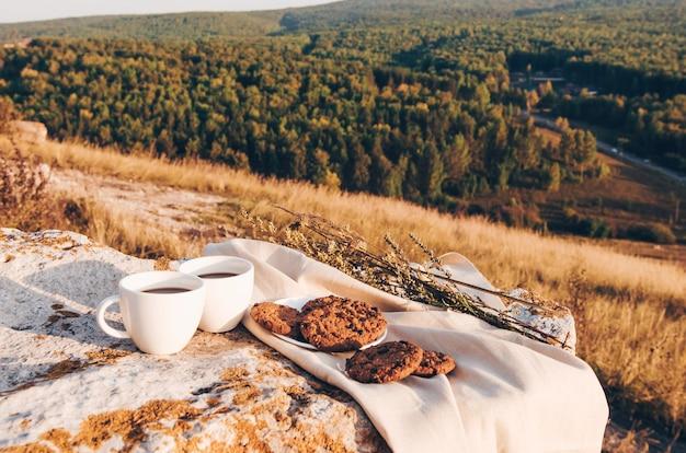 コーヒーカップと自家製クッキーを使った屋外でのピクニックランチ