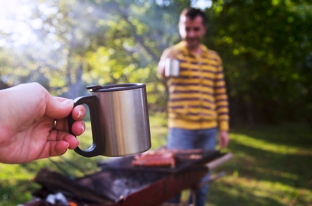 Picnic metal cup in woman hand cheering with male friend on barbecue smoke