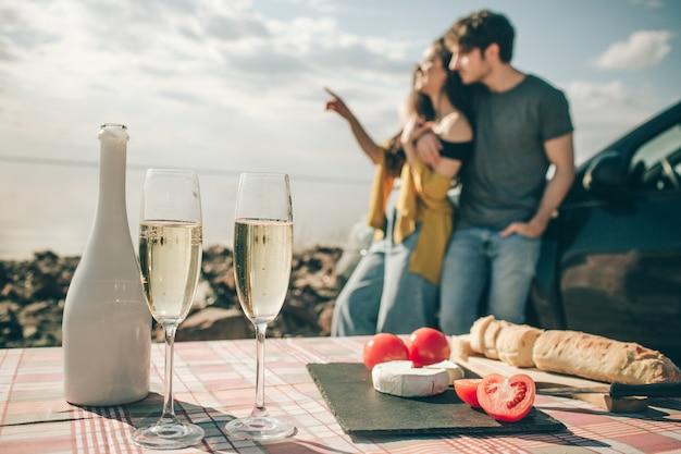 水の近くのピクニック。車でのロードトリップで幸せな家族。負けたバゲット、ホワイトチーズのシャンパントマト。