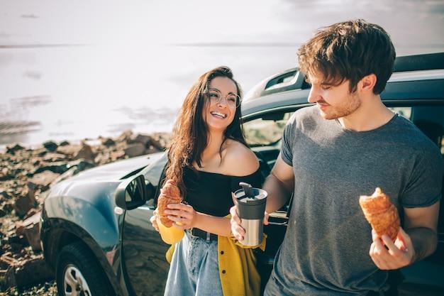 水の近くのピクニック。車でのロードトリップで幸せな家族。男と女は海や海や川を旅しています。自動車で夏に乗る。彼らはおやつに立ち寄った。