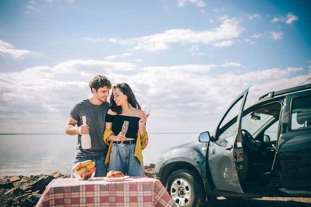 水の近くのピクニック。車でのロードトリップで幸せな家族。男と女は海や海や川を旅しています。自動車で夏に乗る。