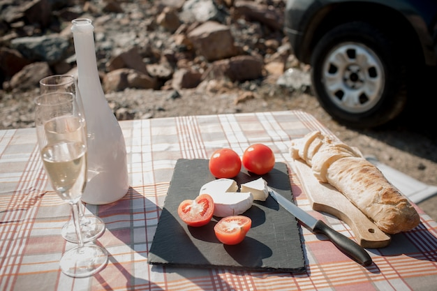 Picnic near the water. happy family on a road trip in their car. lose-up baguette, white cheese champagne tomatoes.