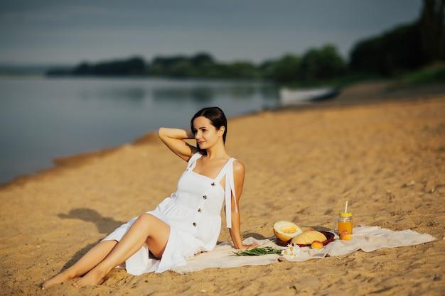 ビーチでのピクニック。夏の晴れた日にビーチのカバーに座っている白いドレスのロマンチックな女性。