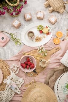 母の日の芝生でのピクニック。果物、アルゼンチンのマテ茶、花を毛布に乗せて。