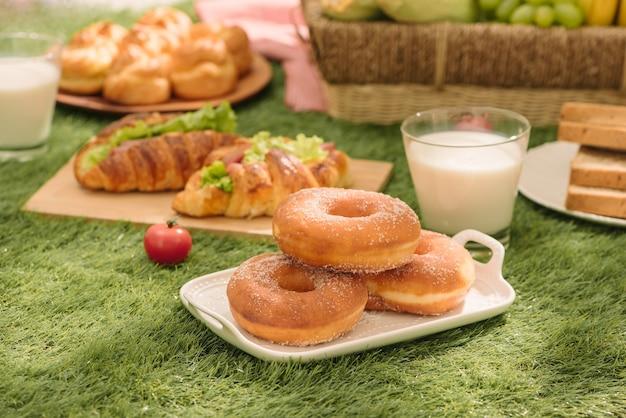 Пикник на траве. красная клетчатая скатерть, корзина, бутерброд здоровой пищи и фрукты, апельсин, молоко. летний отдых.