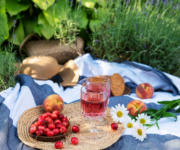 ラベンダー畑での屋外ピクニック。ガラスのロゼワイン、さくらんぼ、毛布の麦わら帽子